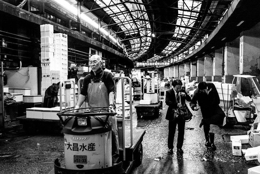 Black and white photo from Tokyo Tsukiji photo book. A man wearing a suit rummages in his bag, another takes off his shoe and checks his foot. An old worker drives a cart.